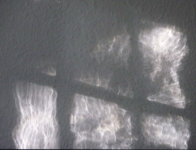 Sunlight through a window reflected on a wall