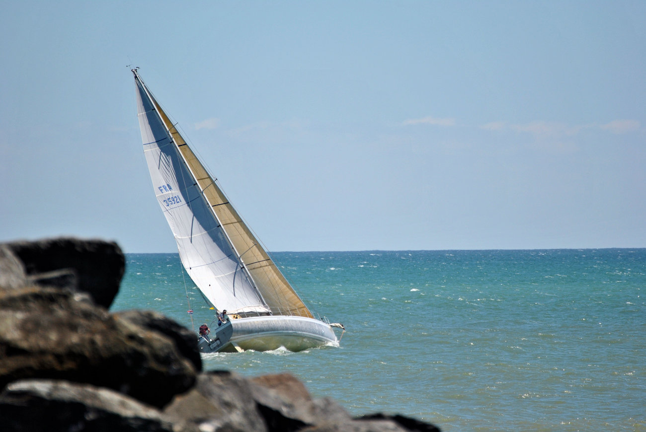 A sailboat leaves the port